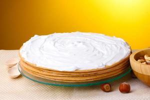 Kuchen und Nüsse auf Tisch auf gelbem Hintergrund foto