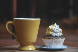 Vintage gelbe Tasse und Cupcake