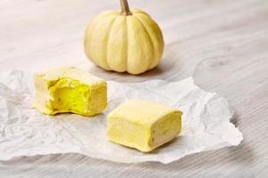 leckere zwei quadratische gelbe Pastell Marsmallows auf Bastelpapier, Biss, foto