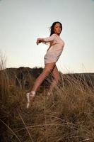 hübsches schwarzes Mädchen, das in der Dünenlandschaft aufwirft. foto