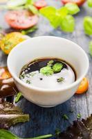 Salatessig in weißer Schüssel mit Basilikumblättern, Nahaufnahme foto