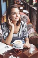 junge Frau, die drinnen im städtischen Café sitzt foto