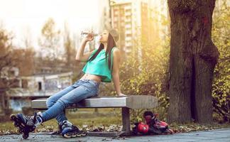 Roller Girl Trinkwasser auf Bank foto