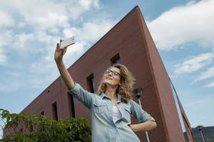 glückliche junge blonde kaukasische Frau, die ein Selfie-Porträt mit nimmt foto