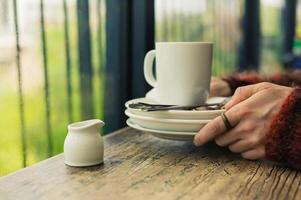 Frau mit leeren Tellern und Becher foto