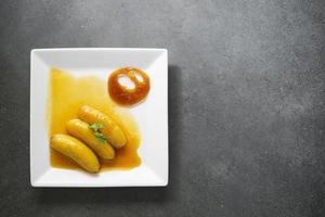 populäres Dessert der Bananenflammbiene auf einfachem modernem Hintergrund foto