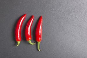 frische Chilis auf schwarzem Schiefer foto