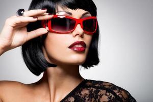 schöne brünette frau mit geschossen frisur mit roter sonnenbrille