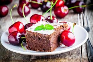 Stück Schokoladen-Brownie-Dessert mit einer Kirsche foto