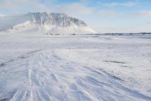 Winterlandschaft mit Bergen, Schnee und kleinen Bauernhäusern, Island foto