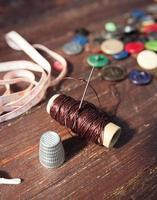 Nähwerkzeuge auf dem alten hölzernen Hintergrund