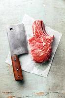 rohes Fleisch und Fleischerbeil foto