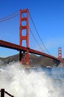 goldene Torbrücke hinter einer brechenden Welle foto