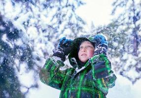 Junge im verschneiten Wald foto