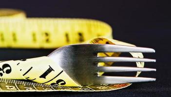Was Sie essen, bestimmt Ihr Gewicht: Gabel mit Maßband foto