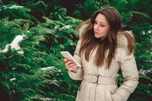 Mädchen im Wald, das Telefon ernsthaft ansieht foto