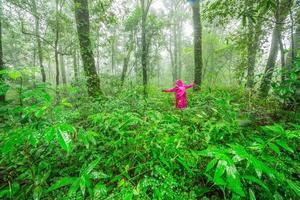 junge Frauen, die im Regenwald stehen foto