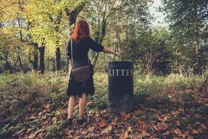 Frau, die Müll im Wald entsorgt foto