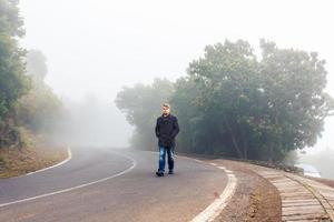 Mann, der in einem nebligen Wald geht foto