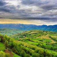 Dorf auf Hangwiese mit Wald im Berg foto