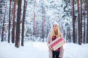 Mädchen, das ein Weihnachtsgeschenk im Winterwald hält foto