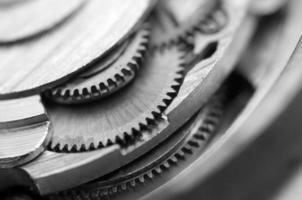 schwarzer weißer metallischer Hintergrund mit Metallzahnrädern ein Uhrwerk foto