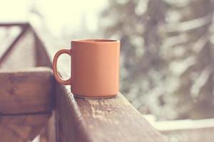 Tasse mit heißem Getränk über Winterwaldhintergrund foto