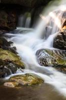 Wasserfall und mit Moos bedeckte Felsen foto