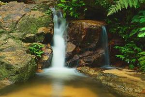 Schön von einem kleinen Wasserfall, der in den Vorderteilen über den Felsen fließt