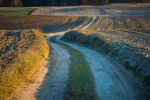 sandige Landstraße und gepflügte Felder foto