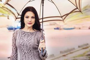 glückliche Frau geht mit einem Regenschirm auf die Brücke