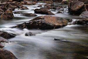 schneller Gebirgsfluss, der zwischen Steinen fließt foto