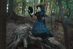 Mädchen im gotischen Kleid, das zwischen den Baumstümpfen steht. foto