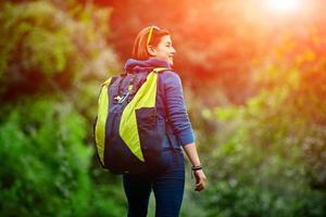 Frauenwanderer lächelnd draußen im Wald mit Rucksack stehend