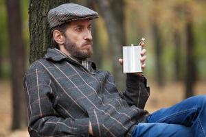 Mann mit Bart sitzt im Herbstwald mit Flasche