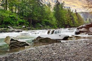 rauer Gebirgsfluss mit weißem Schaum fließt zwischen den Felsen foto