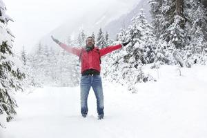 glücklicher junger Mann mit Schneegläsern wirft Schnee auf