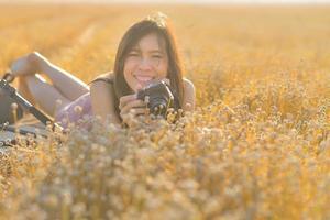 asiatische Frau, die eine Kamera im trockenen Grasfeld hält.