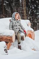Kindermädchen auf gemütlichem warmem Winterspaziergang im Freien im Wald foto