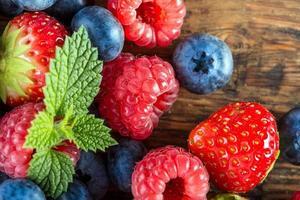 Blaubeeren, Himbeeren, Erdbeeren, Garten- und Waldfrüchte auf Holztisch.