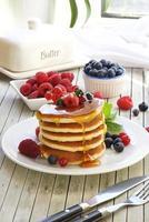 köstlicher Turm aus Pfannkuchen mit wilden Früchten und Sirup