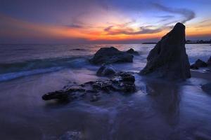 Steinküste mit Wellen Sonnenuntergangslicht.
