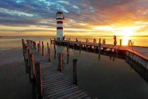 helles schönes Meeressonnenuntergangspanorama über dem Leuchtturm foto