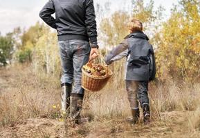 Vater und Sohn tragen einen vollen Pilzkorb foto