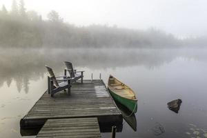 grünes Kanu und Dock an einem nebligen Morgen foto