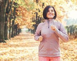 laufendes Mädchenporträt im Herbstpark foto