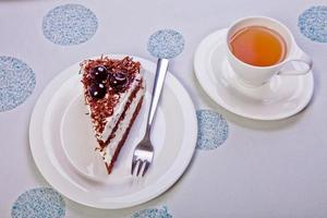 Kuchen mit Schlagsahne und Kirschen dekoriert. isolierter Tee foto