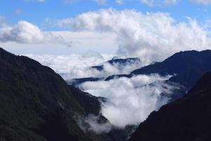 Wolken zwischen Berggipfeln foto