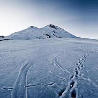 Fußspuren im Schnee am Fuße des Berggipfels foto