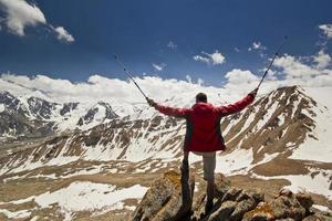 Mann, der auf einer Klippe in den Bergen mit Stangen steht foto